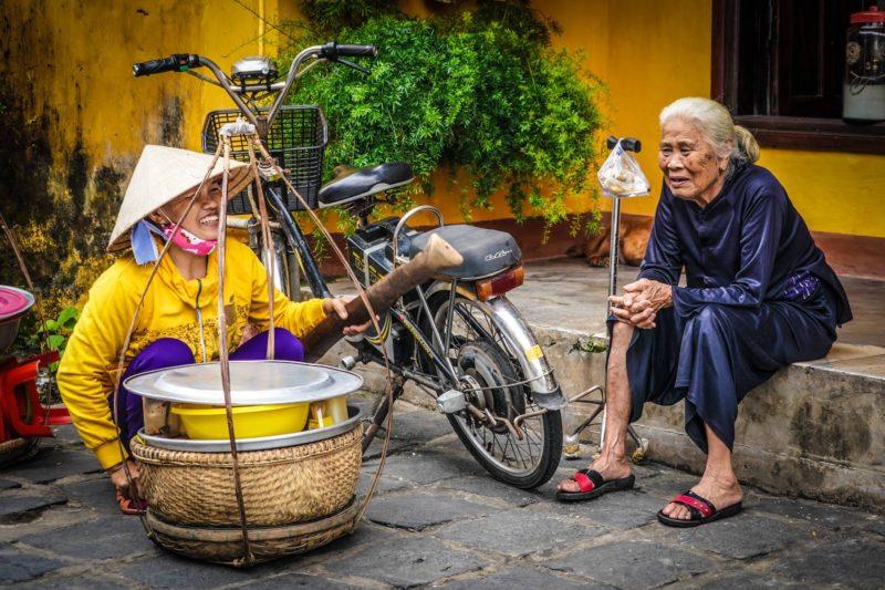 Vietnamese ladies chatting sieving rice
