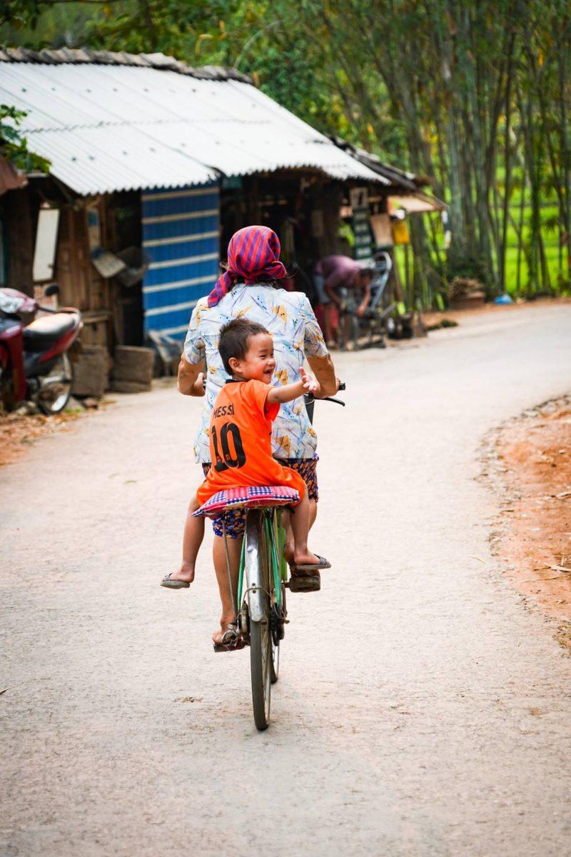 Smiley Vietnamese boy on back of bike waves to friend